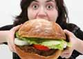 young lady eating huge Burger